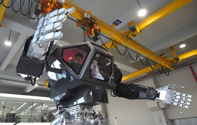 """Engineers test a four-metre-tall humanoid manned robot dubbed Method-2 in a lab of the Hankook Mirae Technology in Gunpo, south of Seoul, on December 27, 2016. The giant human-like robot bears a striking resemblance to the military robots starring in the movie """"Avatar"""" and is claimed as a world first by its creators from a South Korean robotic company. / AFP PHOTO / JUNG Yeon-Je"""